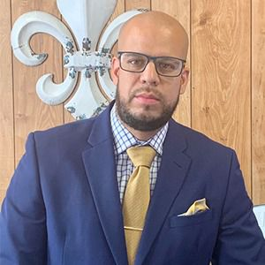 Dr. Alex Marrero, pictured wearing glasses, a blue jacket, checkered shirt and yellow tie.