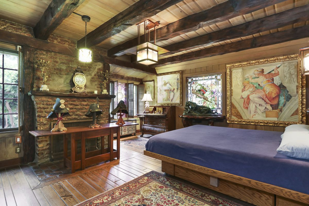 A bedroom with brick fireplace and wood platform bed.