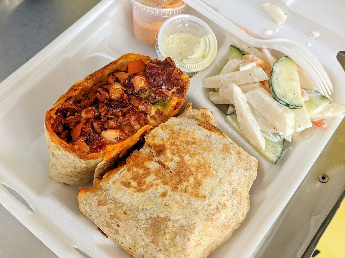 A seafood burrito in deep red sauce, served grilled with avocado on the side.