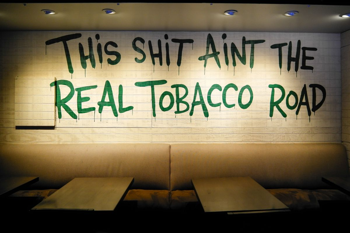 """Tan tables with a white wall that said """"This Shit ain't the real tobacco road"""""""