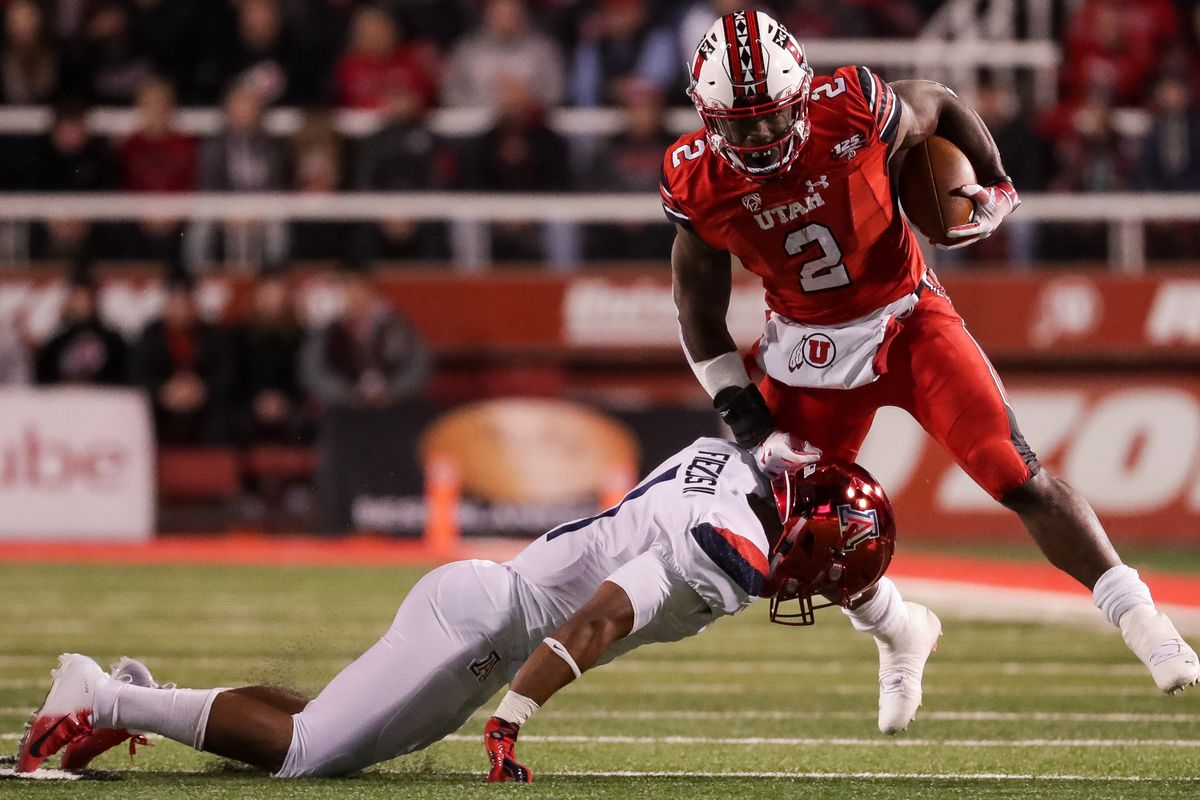 Utah Utes running back Zack Moss (2) evades a tackle from Arizona Wildcats linebacker Tony Fields II (1) during the game at Rice-Eccles Stadium in Salt Lake City on Friday, Oct. 12, 2018.