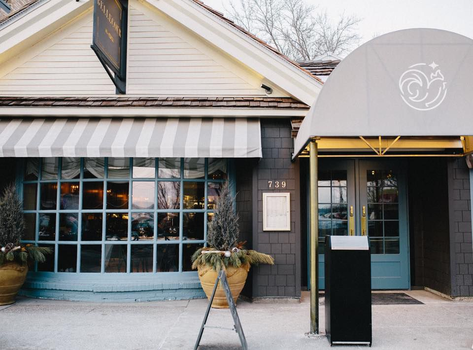 The French country exterior of Bellecour with a gray awning, gold accents, and a light blue trim around the front window