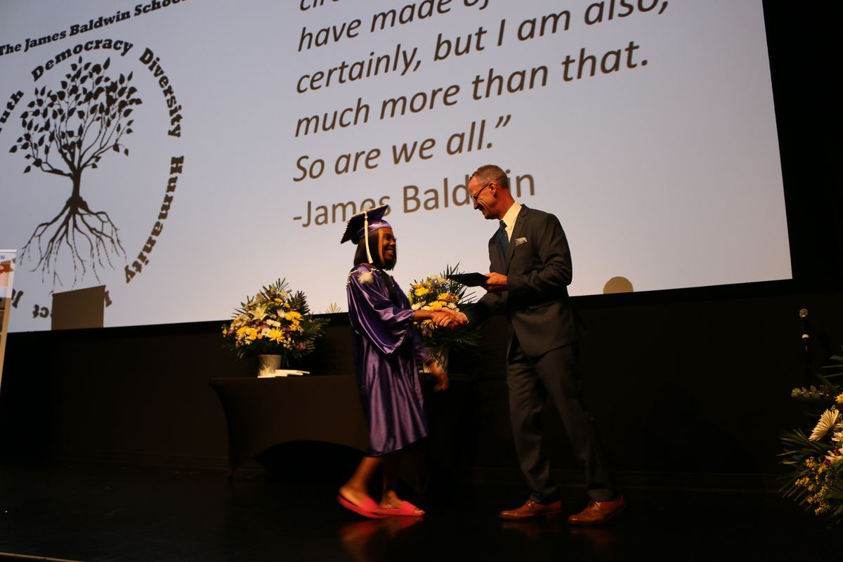 A student receives her diploma from Principal Brady Smith during the James Baldwin School's graduation in June 2019.