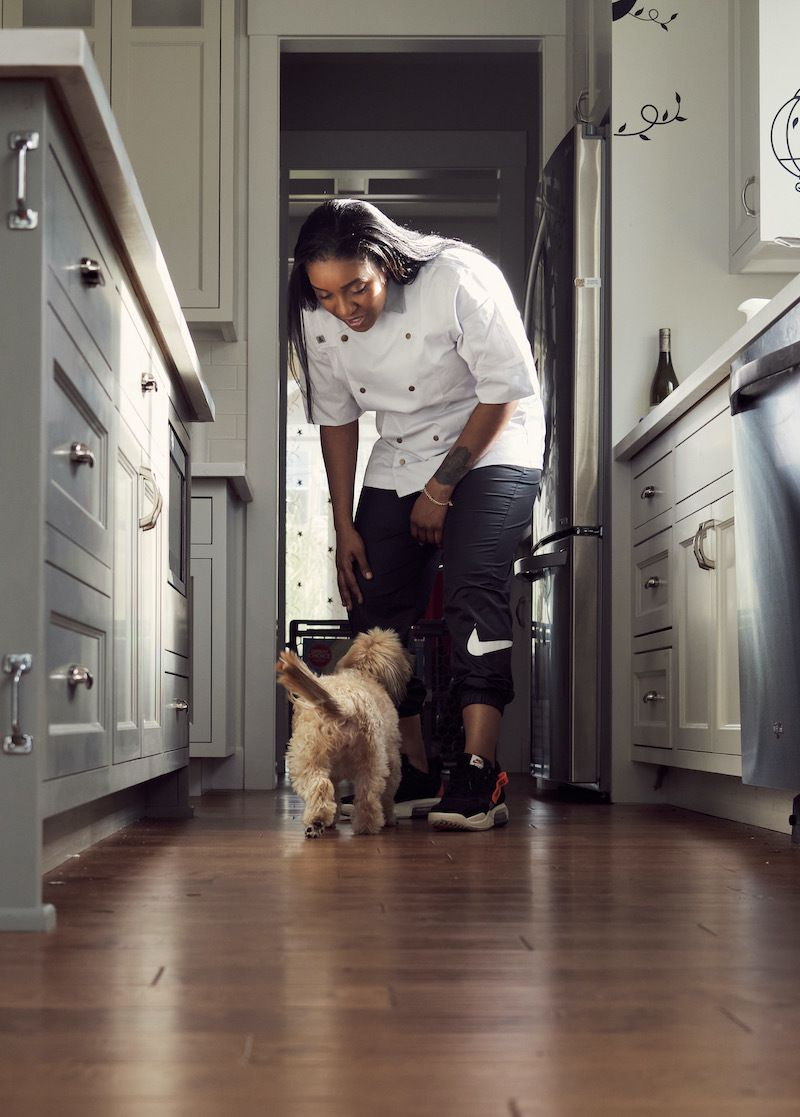 Lex Grant leans down to greet a puppy wearing a chef's coat and Nike basketball shorts
