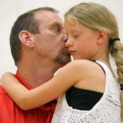 Larry Krystkowiak, head coach for the Utah Runnin' Utes basketball team, kisses his daughter Sam at the University of Utah in Salt Lake City on Friday, June 12, 2015.