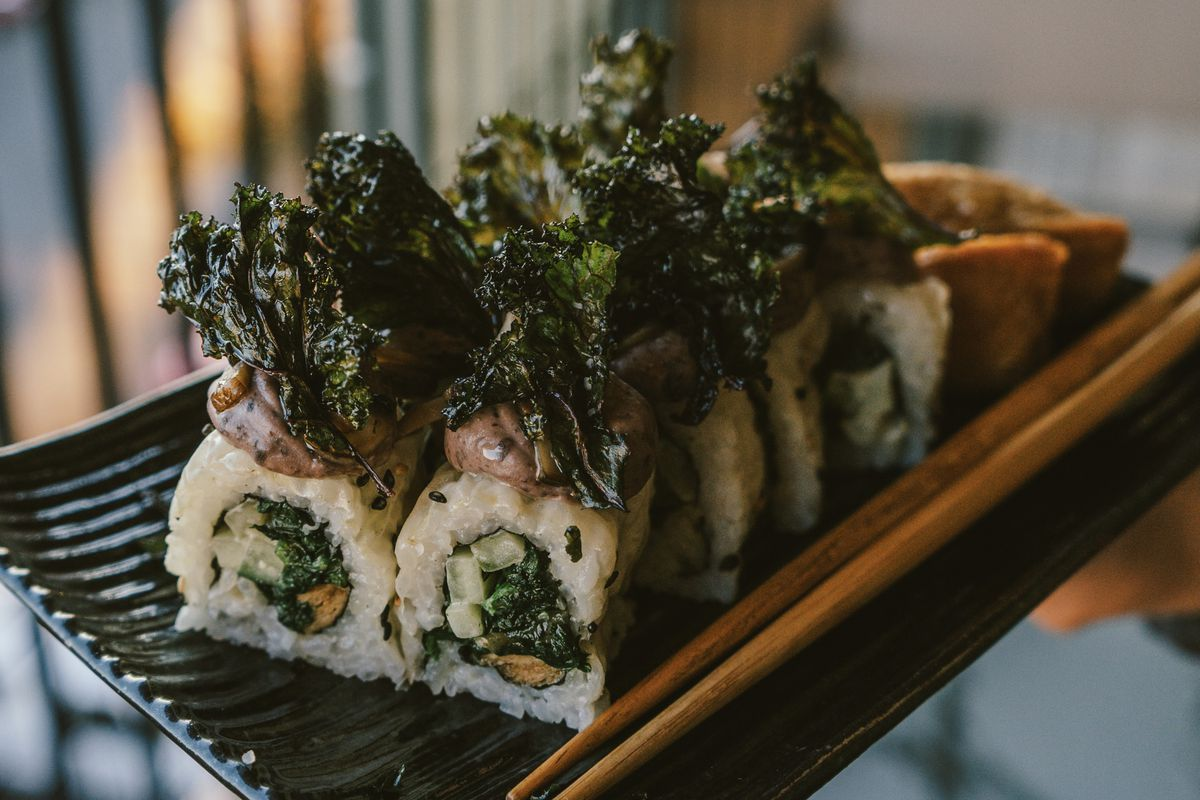 A platter holds a vegan sushi roll, topped with large pieces of seaweed