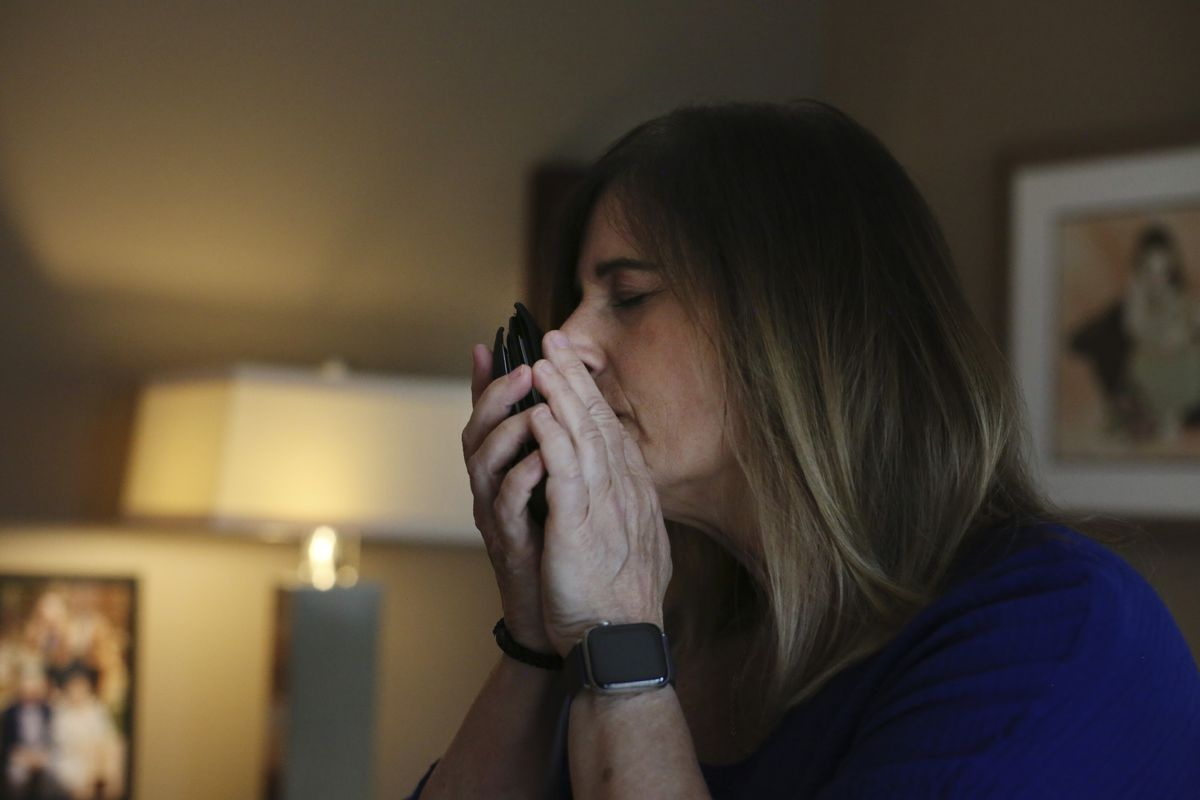 Michelle Pepe tries to smell her late father's wallet while going through his belongings one year after he died of the coronavirus, in Sharon, Mass., on Wednesday, April 14, 2021. After contracting the virus herself, Pepe lost and has not regained her sense of smell. She keeps her father's belongings in hopes that one day it comes back and she can smell him again.