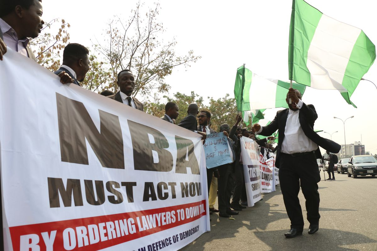 "People holding a banner that reads ""NBA must act now"" protest the suspension of Nigeria's Chief Justice Walter Nkanu Samuel Onnoghen, in Abuja, Nigeria,"
