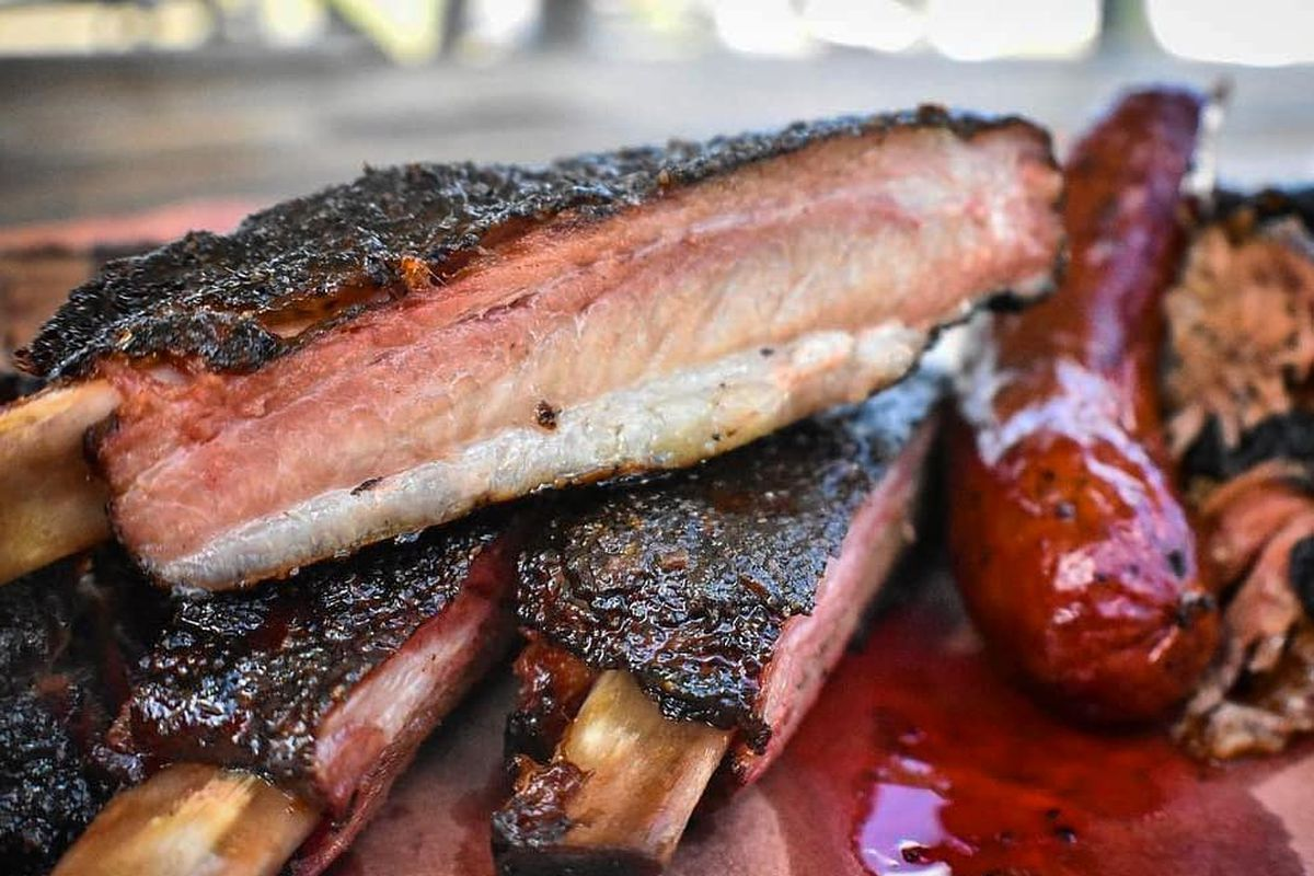 Close up of ribs stacked on greasy red butcher paper next to a link of sausage