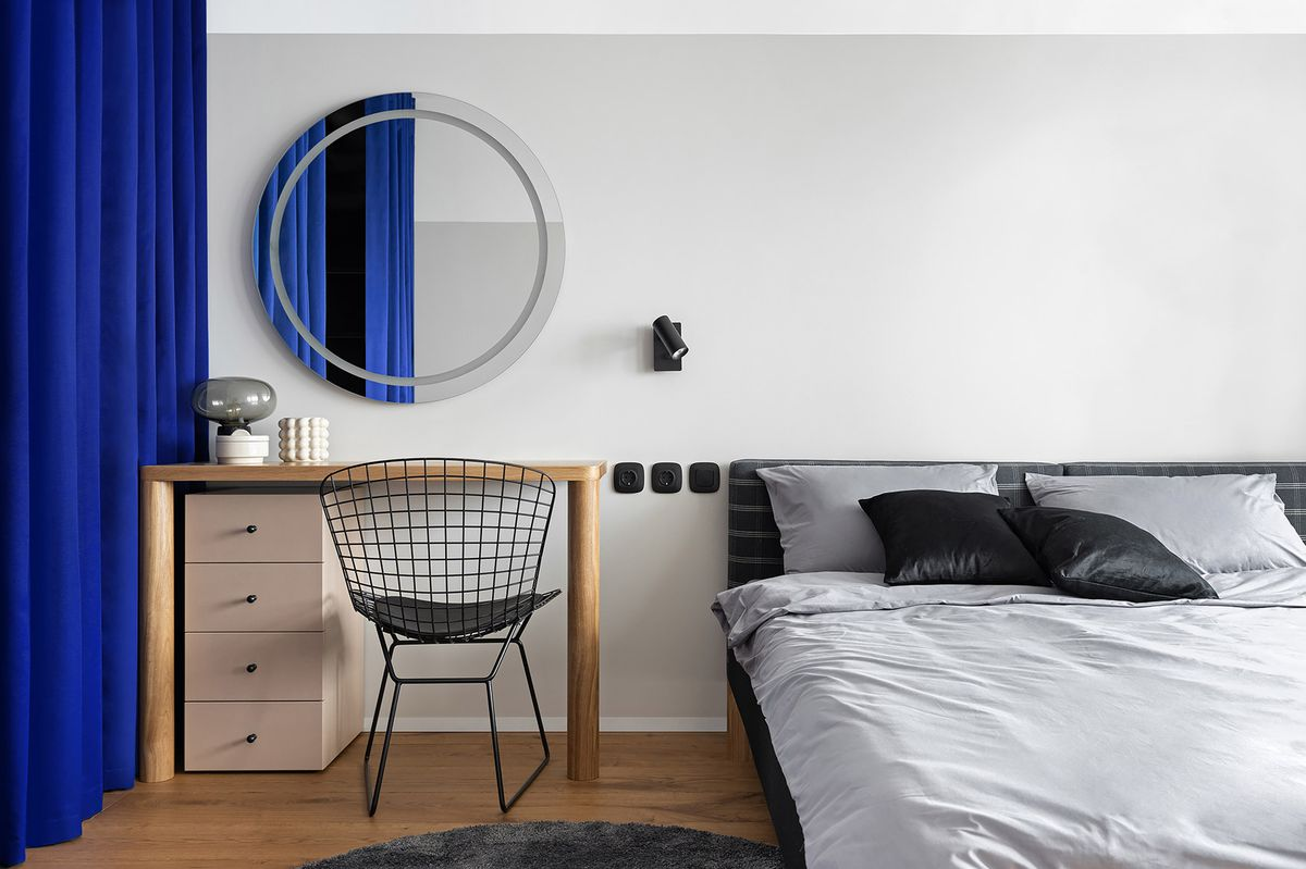 Bedroom with a bed, wooden desk, and round mirror.