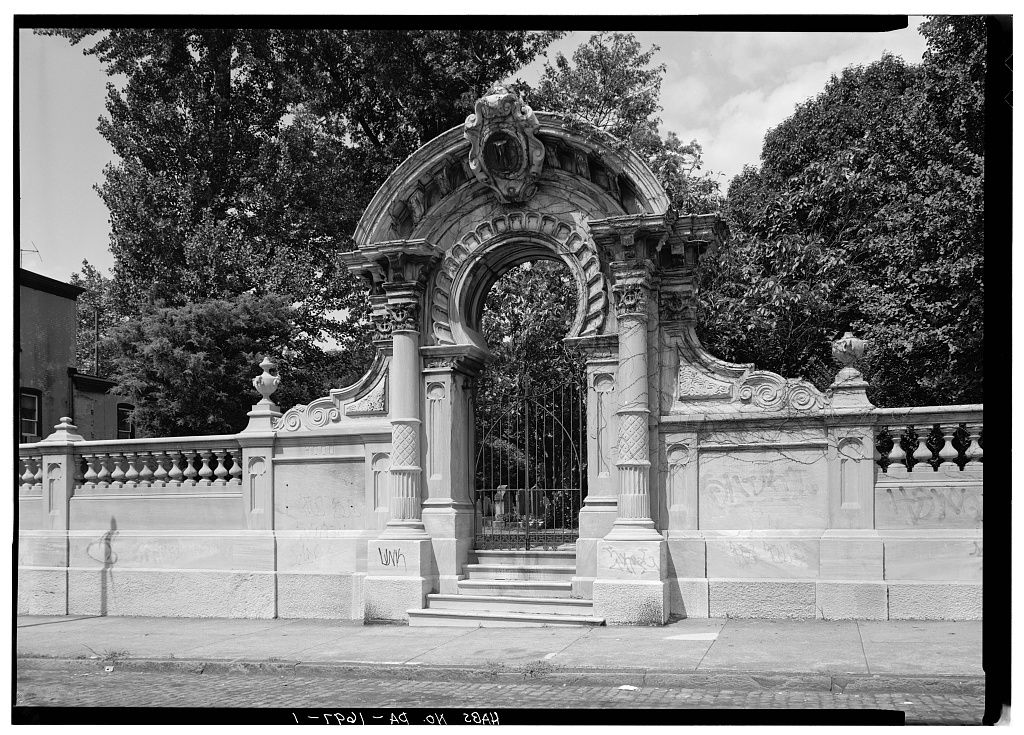 The entrance to Hood Cemetery in Philadelphia. There is a fence and an arched entryway. Behind the entryway are trees.
