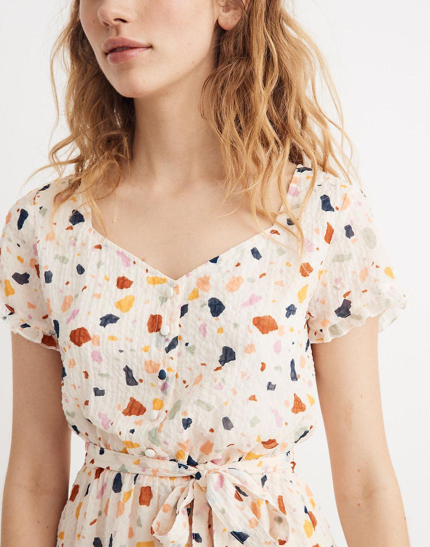 A model wearing a terrazzo-patterned summer dress.