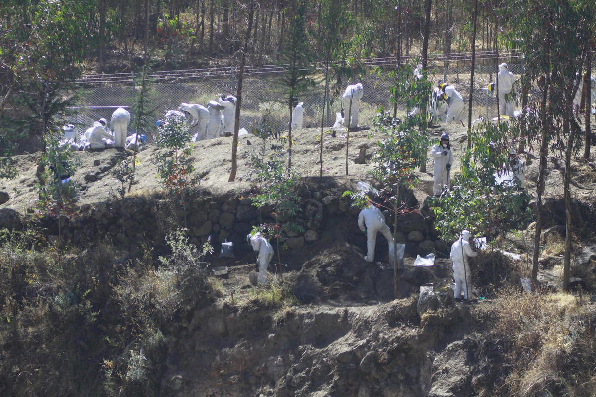 FILE - In this July 31, 2012 file photo, workers from the Antamina copper mine, wearing white uniforms, clean the river in Cajacay, Peru.  A pipeline carrying copper concentrate laced with volatile compounds burst open on July 25. More than a month after