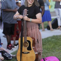 """Lottie Johnson, Deseret News arts and entertainment assistant editor, picks up her guitar while waiting for """"American Idol"""" auditions outside of the Northwest Community Center in Salt Lake City on Thursday, Aug. 29, 2019."""