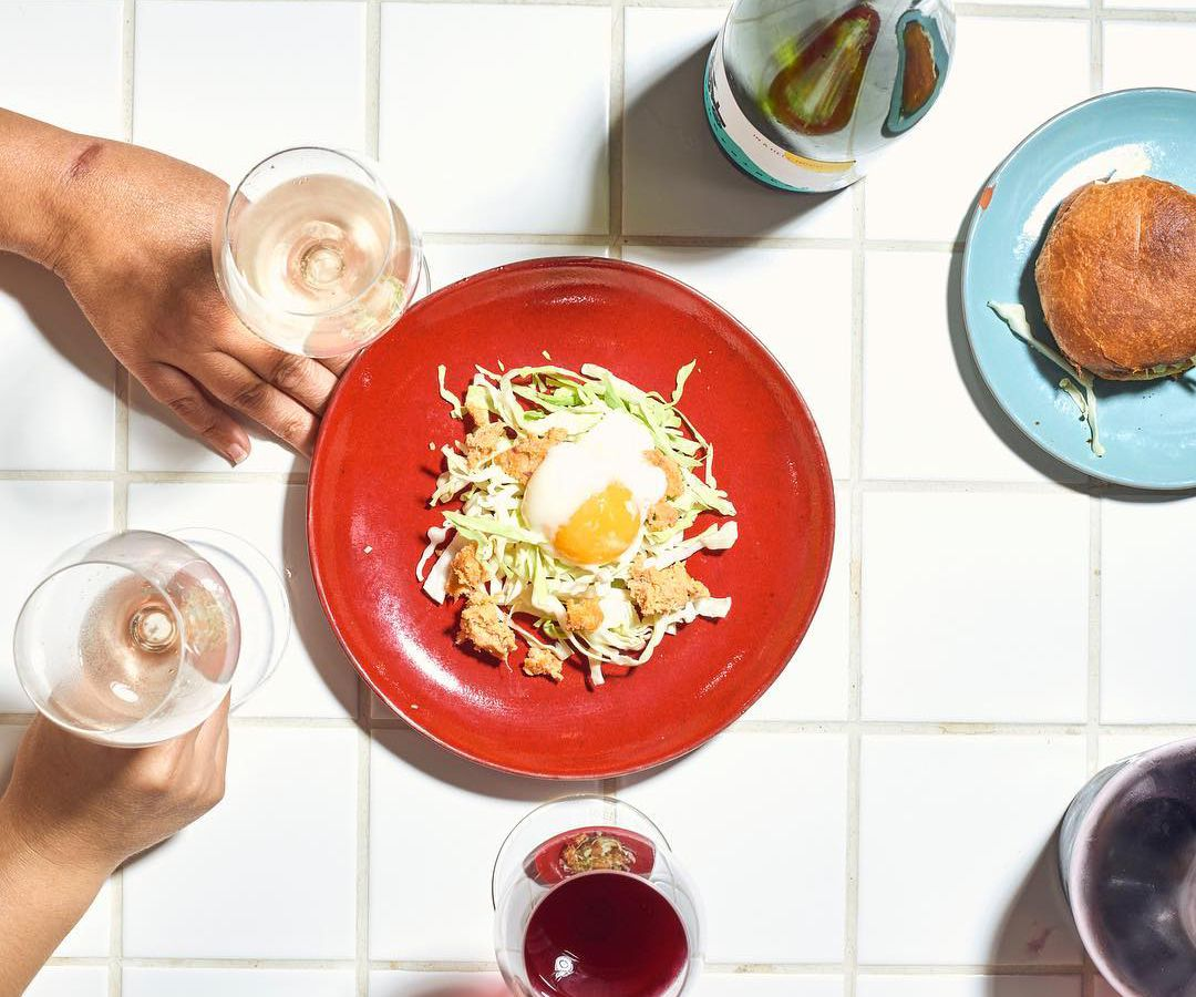 A tiled tabletop seen from above with a plate of cabbage salad dotted with croutons and a runny egg, and another plate with a sandwich, as well as hands holding glasses of white and red wine.