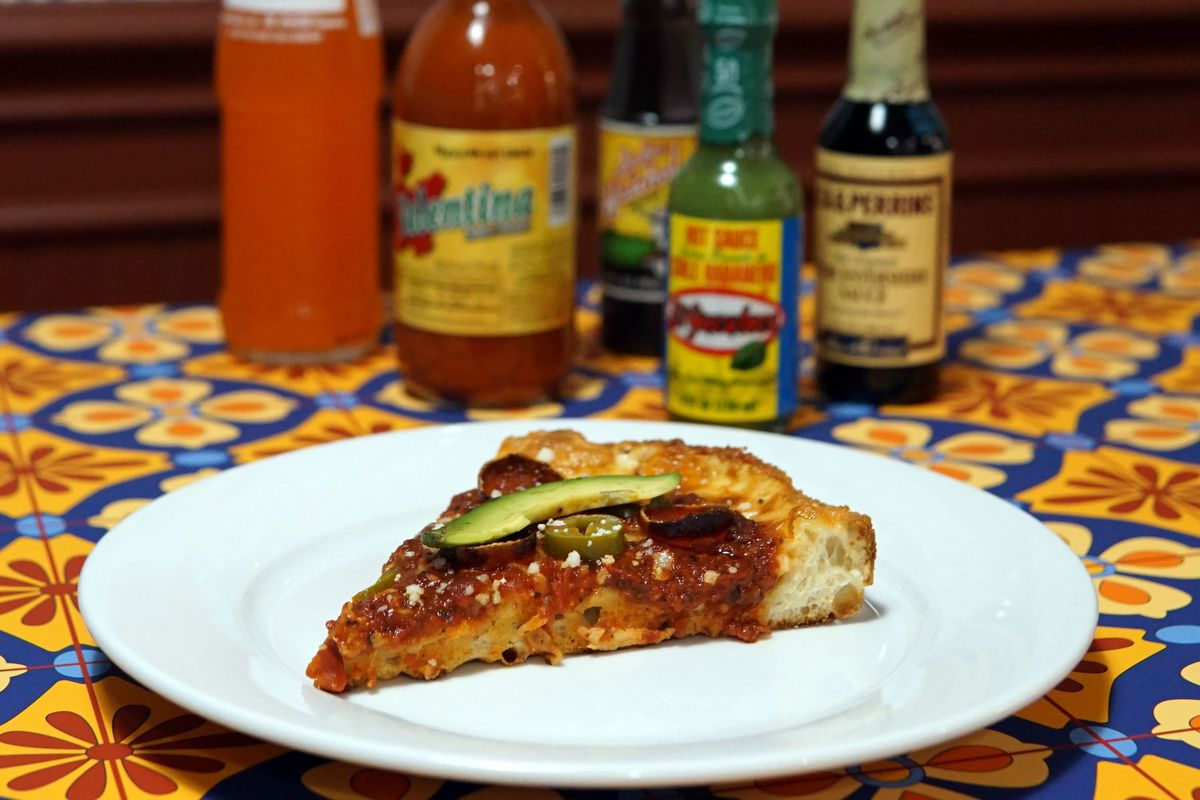 A picture of a slice of pizza at Zapapizza surrounded by hot sauces and a Fanta