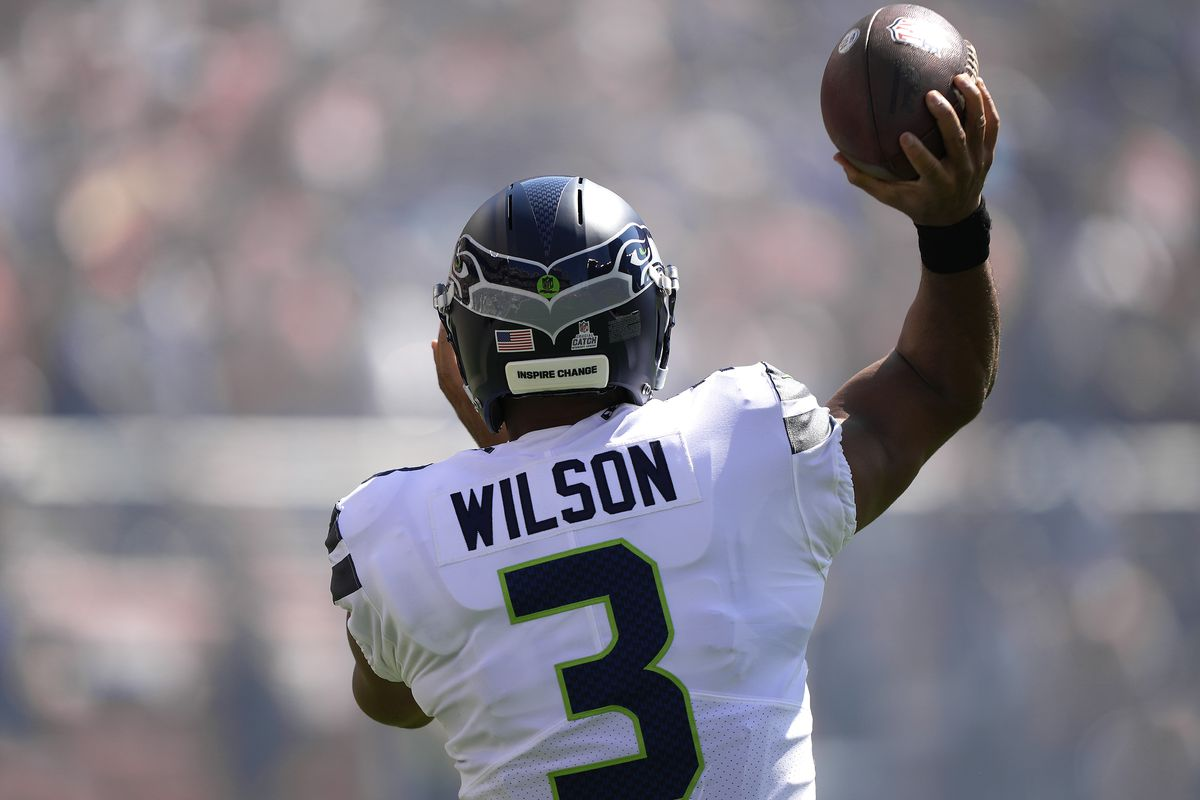 """Russell Wilson #3 of the Seattle Seahawks with the words """"Inspire Change"""" on the back of his helmet warms up on the field prior the start of the game against the San Francisco 49ers at Levi's Stadium on October 03, 2021 in Santa Clara, California."""