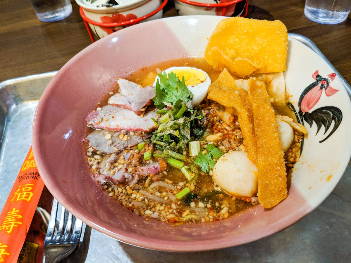 Soup in a Thai-style bowl decorated with a rooster. There are pink barbecue pork slices in the soup, as well as an egg, ground pork, ground peanuts, crispy wonton strips, and more. The bowl sits on a metal tray.