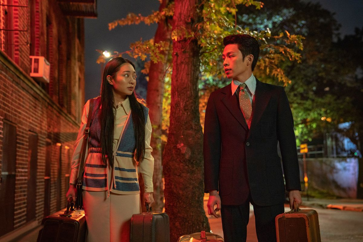 a man and woman stand holding suitcases