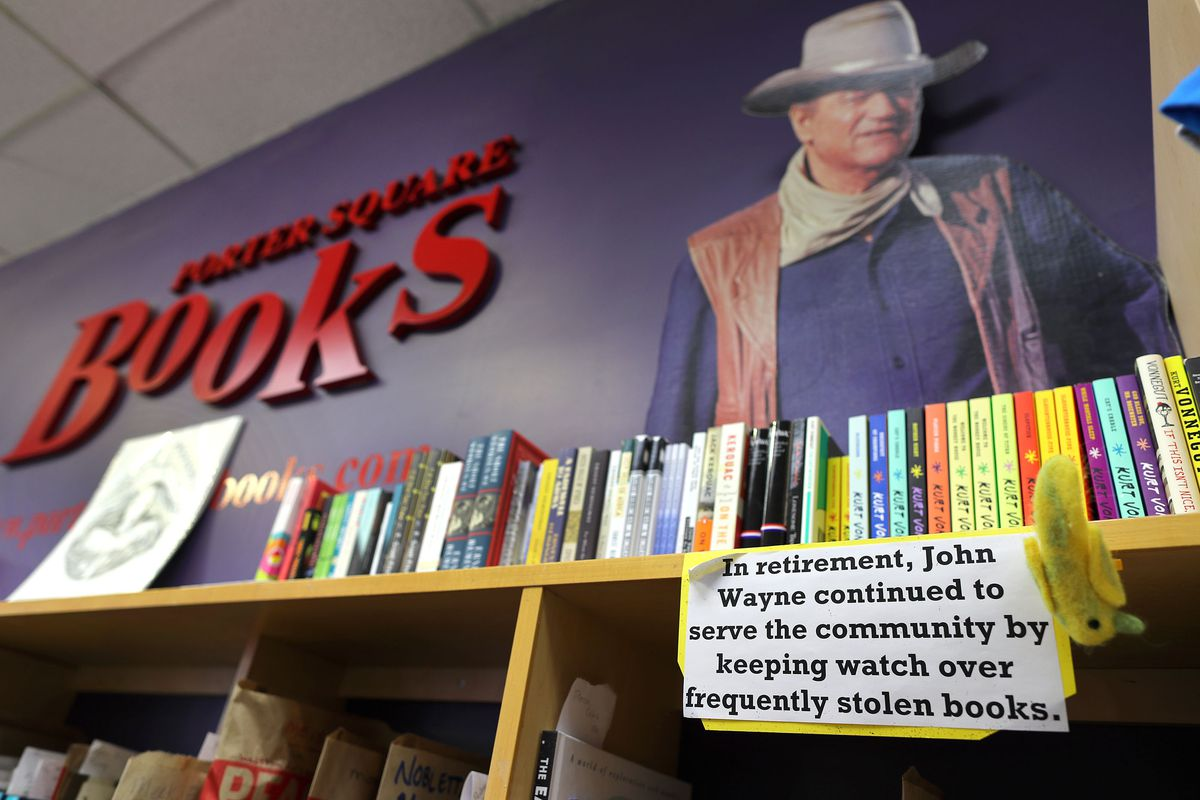 """A run of bookshelves with a cutout of a cowboy above it and a sign reading, """"In retirement, John Wayne continued to serve the community by keeping watch over frequently stolen books."""""""
