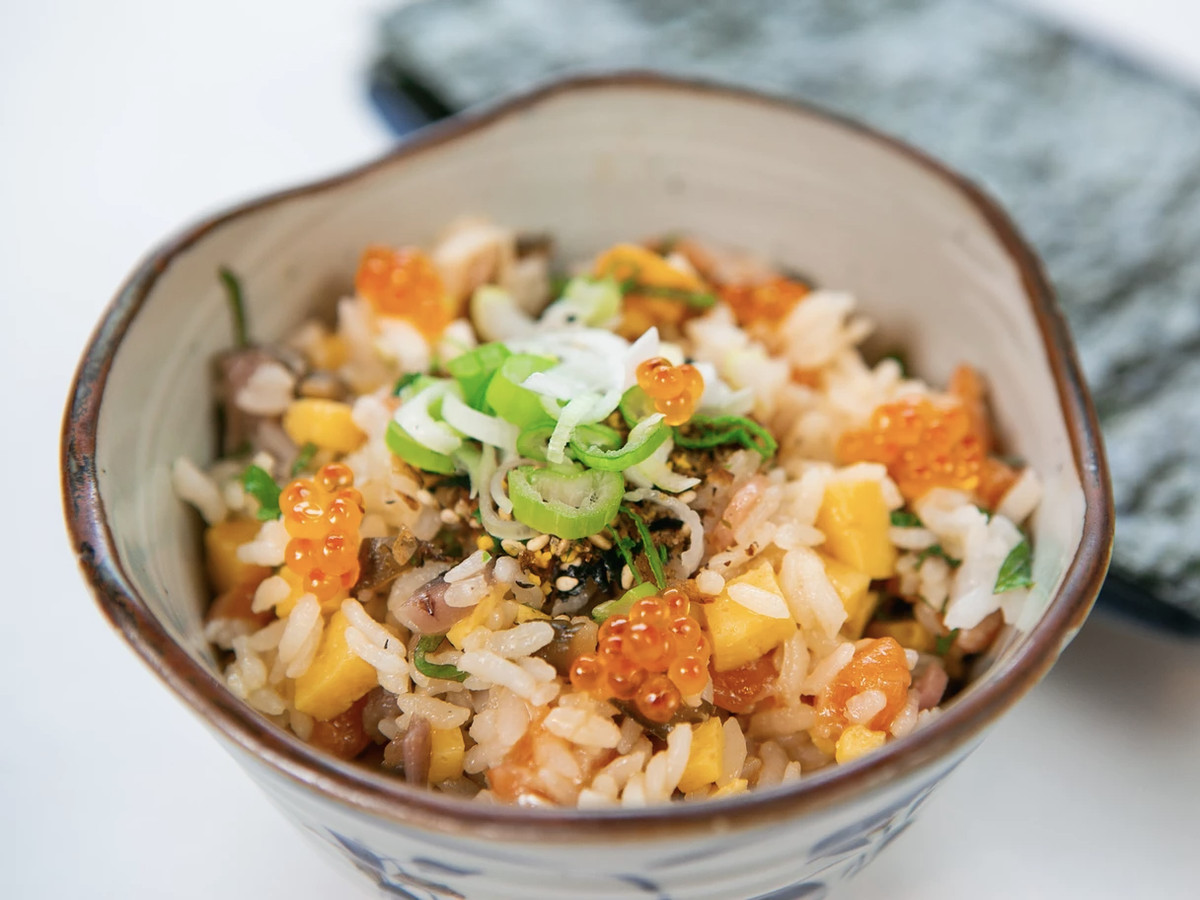 A bowl of salmon, sushi rice, tamago, shiso, shibazuke, and nori.