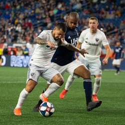 FOXBOROUGH, MA - MAY 25: D.C. United midfielder Luciano Acosta #10 tries to dribble by New England Revolution defender Andrew Farrell #2 during the second half at Gillette Stadium on May 25, 2019 in Foxborough, Massachusetts. (Photo by J. Alexander Dolan - The Bent Musket)