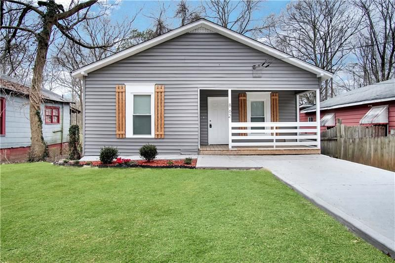 Gray house with white trim, wood shutters, concrete driveway and green lawn.
