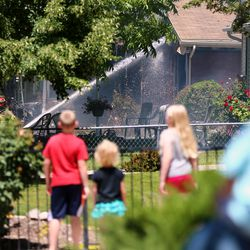 Kids watch from a distance as Unified Fire Authority firefighters spray water into a home while fighting a fire at 3381 S. 3170 East in Millcreek on Sunday, July 5, 2020.