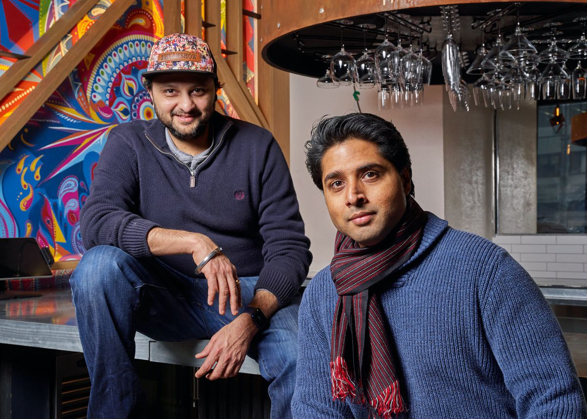 Two men, the chef and owner of Dhamaka, sit side by side for a portrait