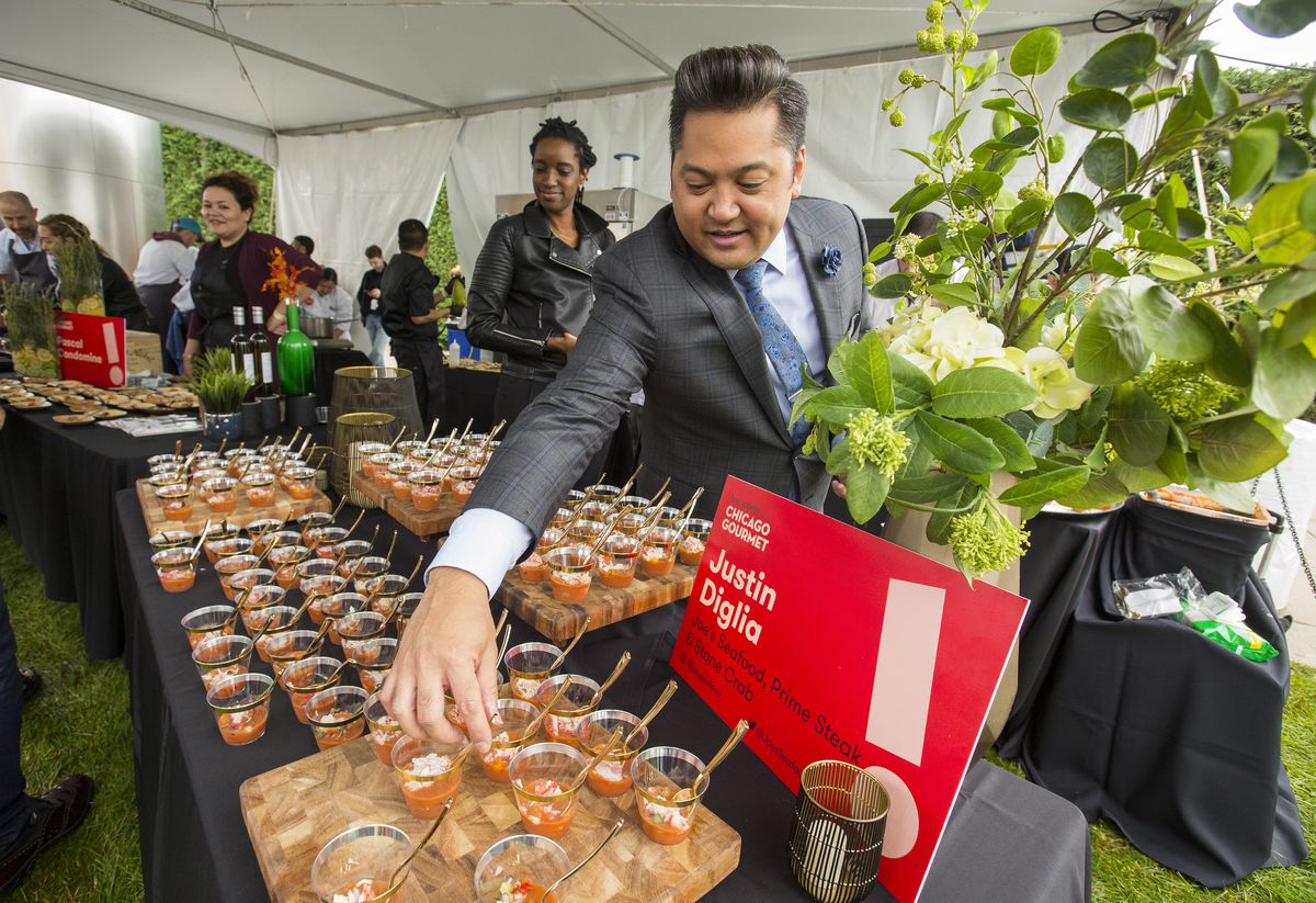A man arranges tasting cups with spoons on a table at Chicago Gourmet.