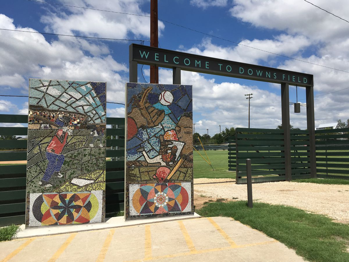 Entrance to small outdoor baseball field with mosaic murals