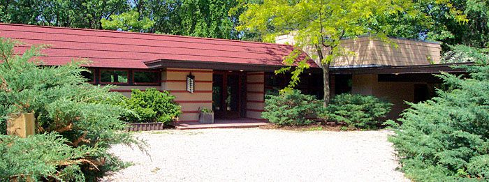 The exterior of Frank Lloyd Wright's Van Tamelen House. The facade is tan brick with a red roof.