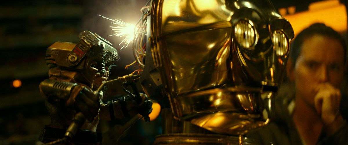 Babu Frik doing surgery on the back of C-3PO's opened head as Rey looks on in Star Wars: The Rise of Skywalker