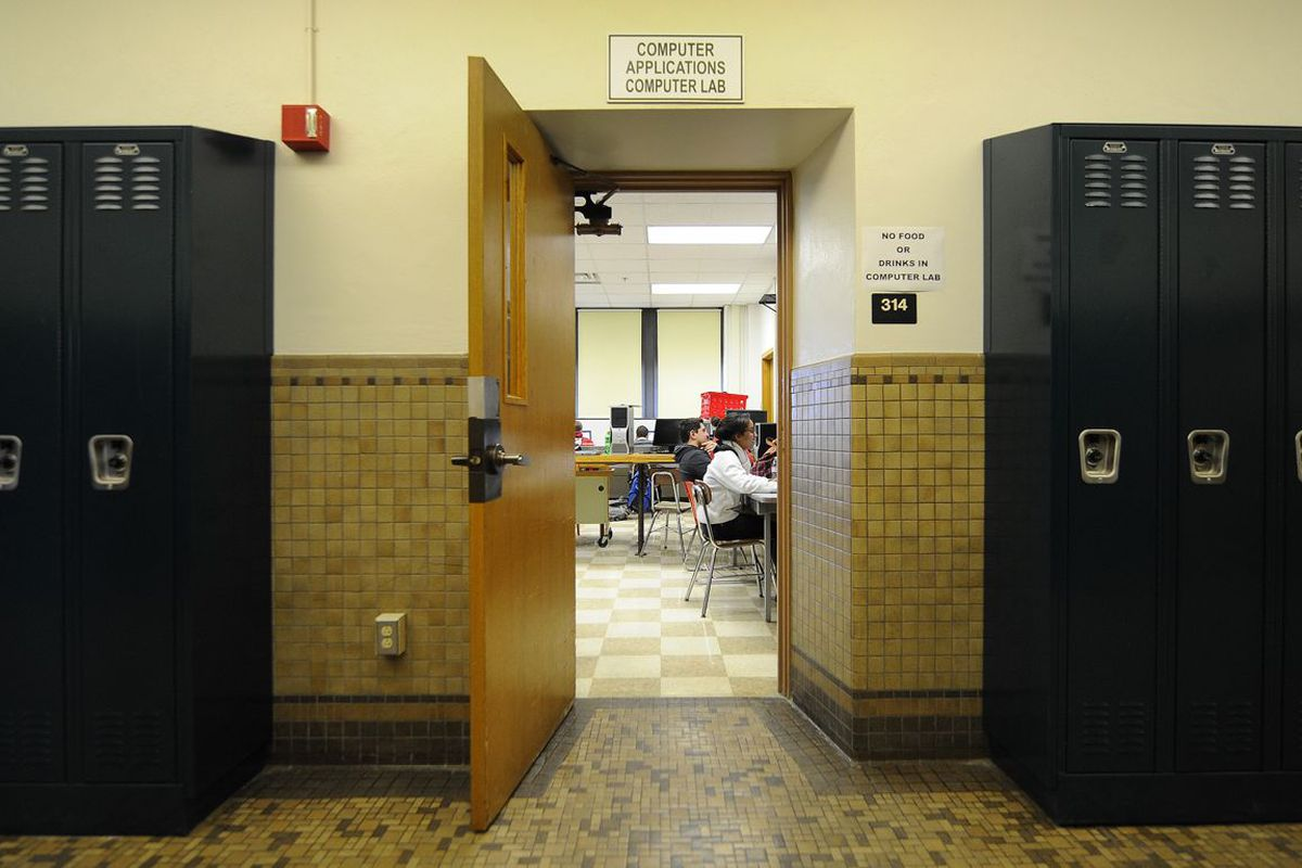 Through an open door from a room with lockers one can see people sitting in a computer lab in a school.