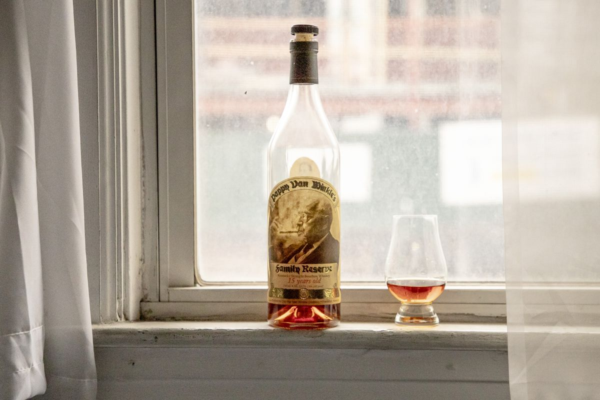 A bottle of Pappy Van Winkle in a window, next to a glass filled with a little bit of bourbon.
