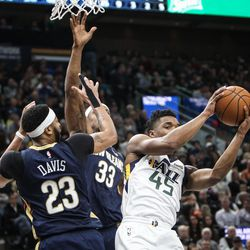 Utah Jazz guard Donovan Mitchell (45) pulls down a rebound against New Orleans Pelicans forward Anthony Davis (23) and forward Dante Cunningham (33) as Utah hosts New Orleans at Vivint Arena in Salt Lake on Friday, Dec. 1, 2017.