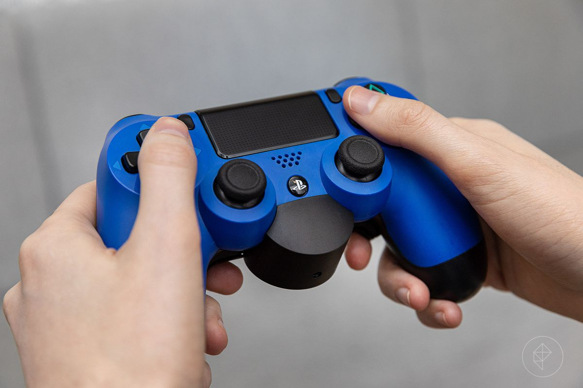 Two hands holding the Sony PS4 controller with the DualShock 4 Back Button Attachment.