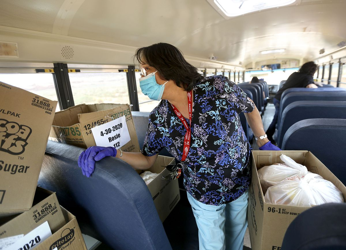 LaVerne Juan, a bus driver and bus aide, helps load boxes of food onto a school bus in Oljato-Monument Valley, San Juan County, on Thursday, April 30, 2020. While schools are closed due to COVID-19, school bus drivers are delivering homework and food to students two days a week. The Navajo Nation has one of the highest per capita COVID-19 infection rates in the country.
