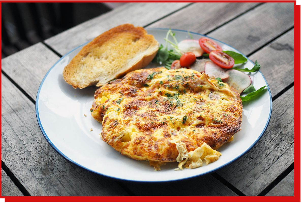 Round frittata on a plate with salad and piece of bread.