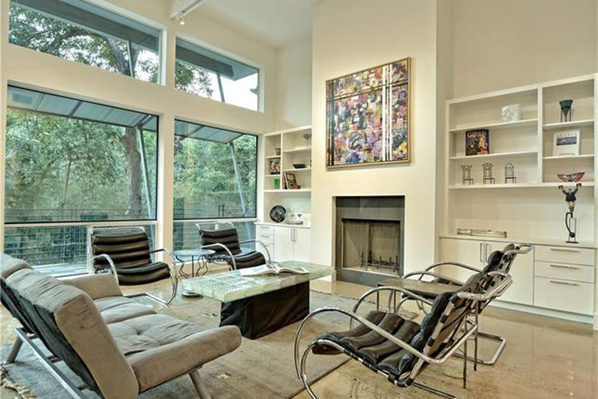 Large contemporary living room white with very high, vaulted ceiling and big windows looking out over woods