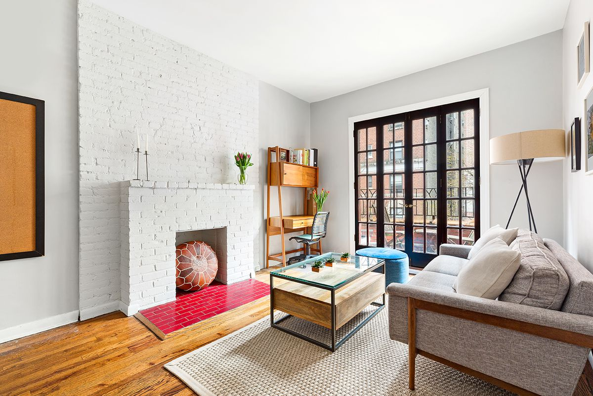 A living area with exposed brick, a door that leads to a balcony, a light brown couch, and a glass and wood coffee table.