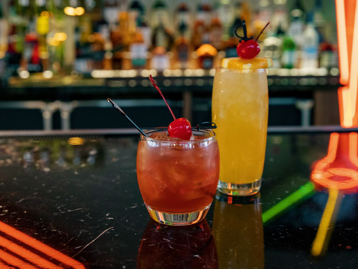 A brown Old Fashioned in a short curved glass features a black swizzle stick and a red maraschino cherry. It stands next to a yellow Walbanger in a tall curved glass with an orange slice and cherry garnish on top. Neon lights reflect off the counter.