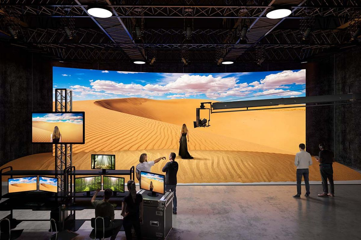 Image of an actress standing in front of a display wall being used as a virtual set