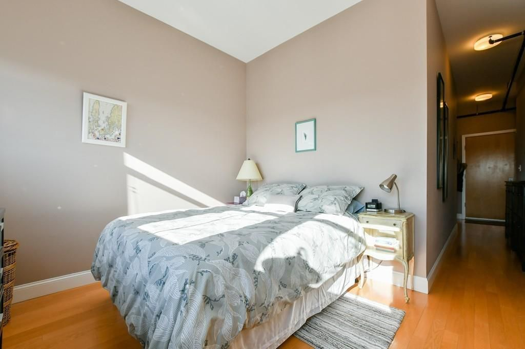 A bedroom with a bed next to a narrow entryway leading to the room's closed door.