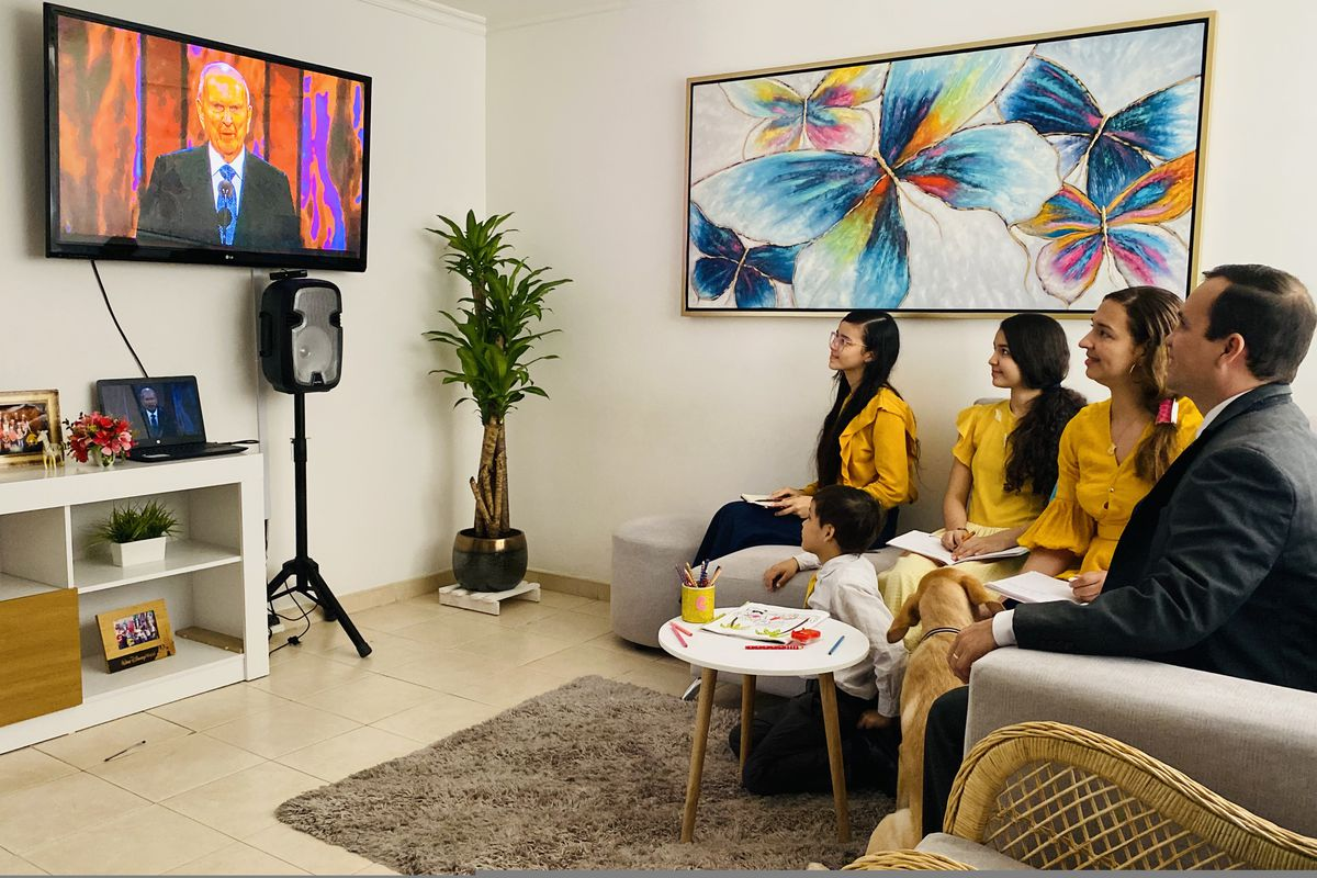 Latter-day Saints in Colombia watch a session of general conference on their television in April 2021.