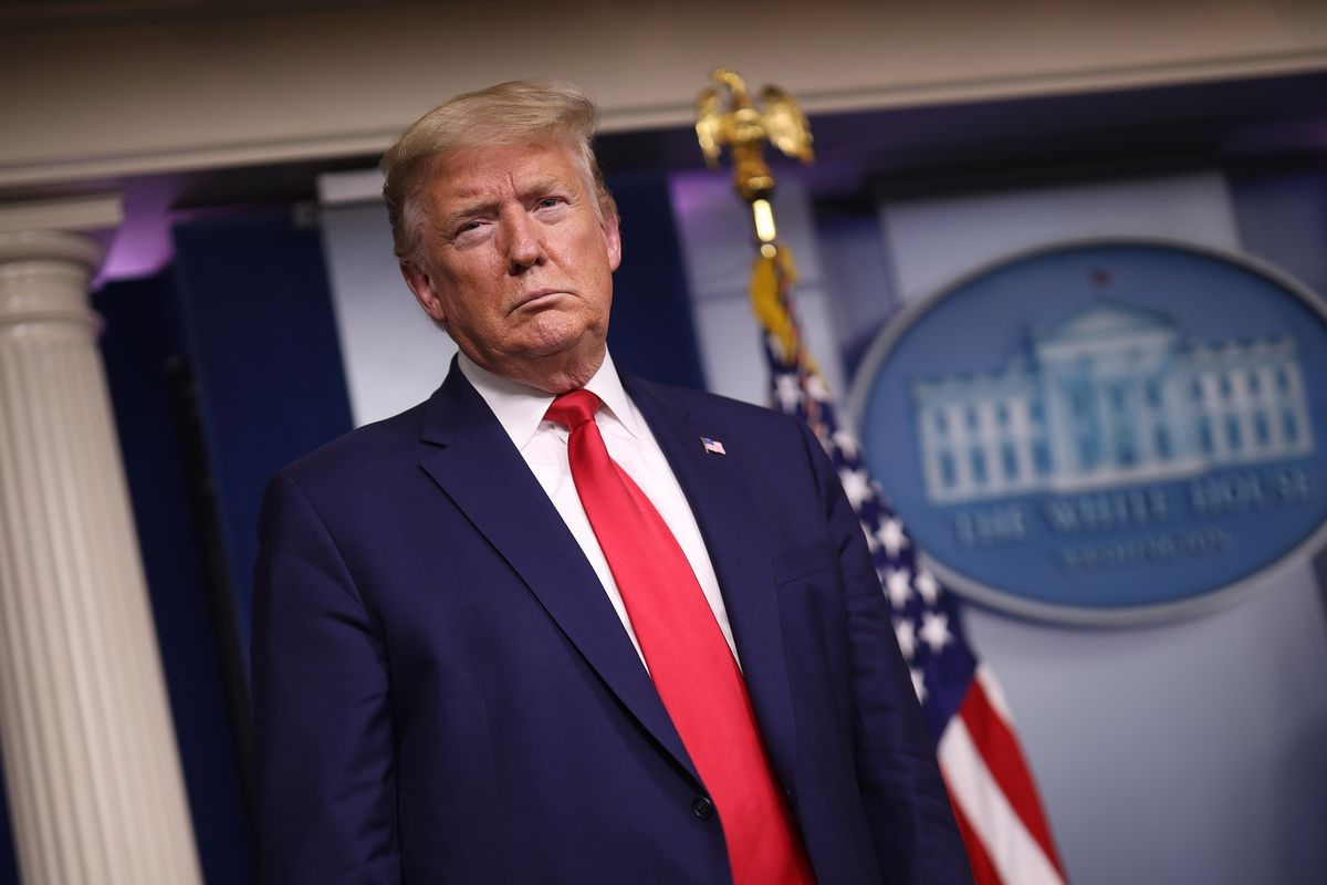 President Donald Trump, in a navy suit and red tie, listens to officials at a press briefing, the American flag behind him.