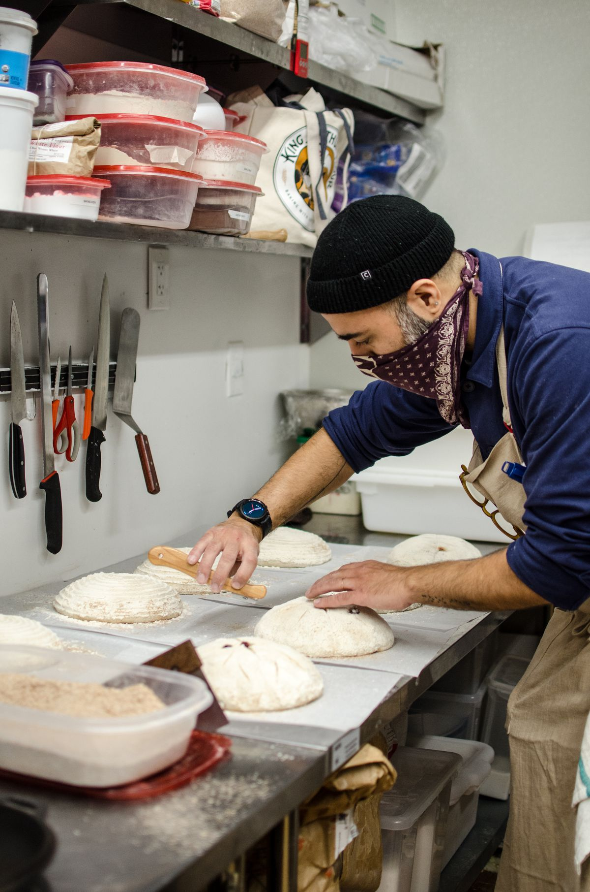 A man bends over a countertop in a kitchen, scoring uncooked round loaves of bread. He wears a handkerchief over his face due to COVID restrictions.