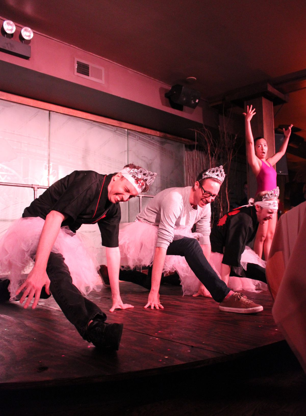 """As a punishment for losing the beer chugging contest, BATSU! cast members Eric Robinson (left) and Nate Mount (right) along with audience member Matthew Robinson (center) had to demonstrate ballet moves directed by """"Samantha San,"""" including plies, twirls"""