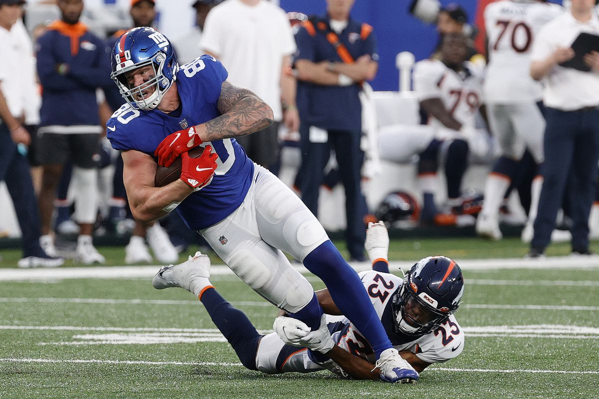 Kyle Rudolph #80 of the New York Giants is tackled by Kyle Fuller #23 of the Denver Broncos during the second half at MetLife Stadium on September 12, 2021 in East Rutherford, New Jersey.