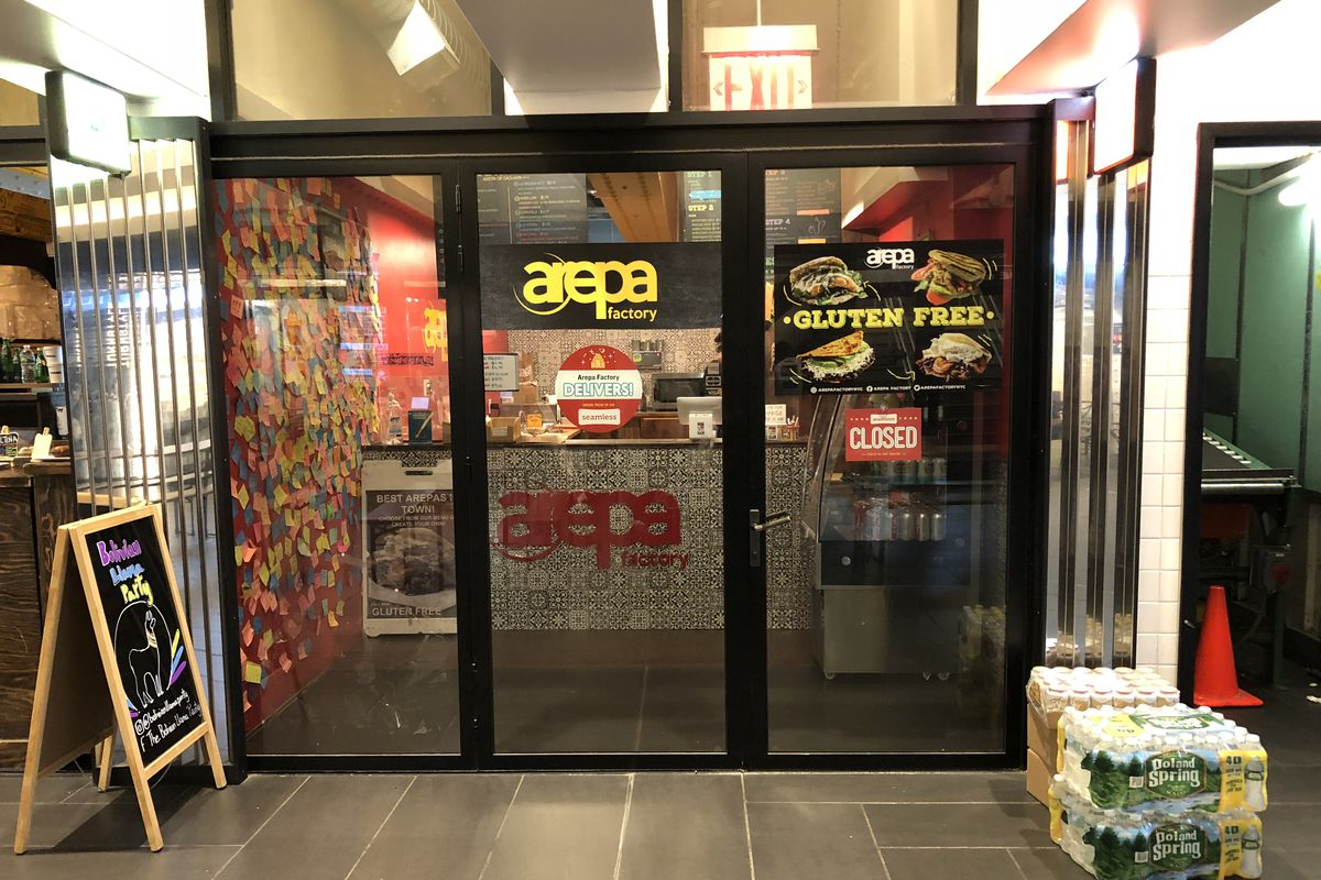 """An underground storefront with a glass doors and a sign that reads: """"arepa factory"""""""